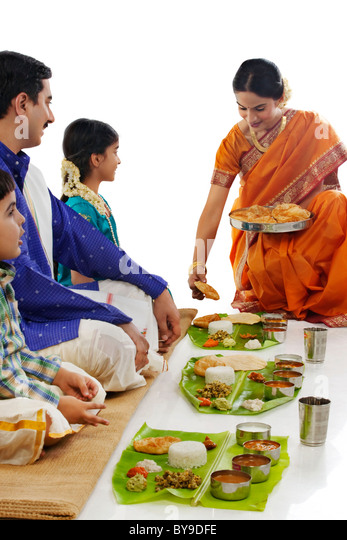 South Indian woman serving food to her family - Stock Image