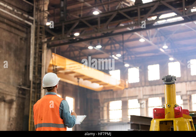 Steel worker with clipboard looking up in factory - Stock Image