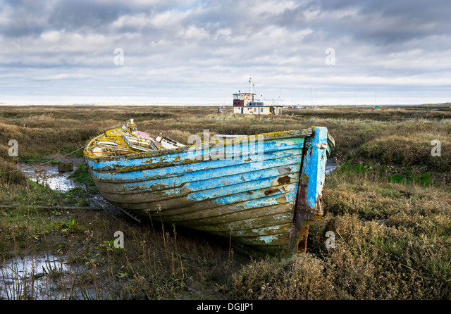The remains of an old wooden dinghy abandoned in the Tollesbury Saltings. - Stock Image