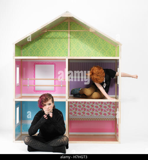 Serious teen girl and school boy playing in a giant doll house - Stock Image