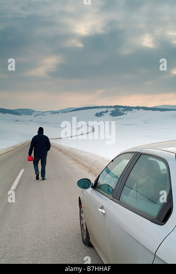 Man Starts the Long Walk Along an Isolated Country Road in Winter to Find Fuel for His Broken Down Car - Stock Image