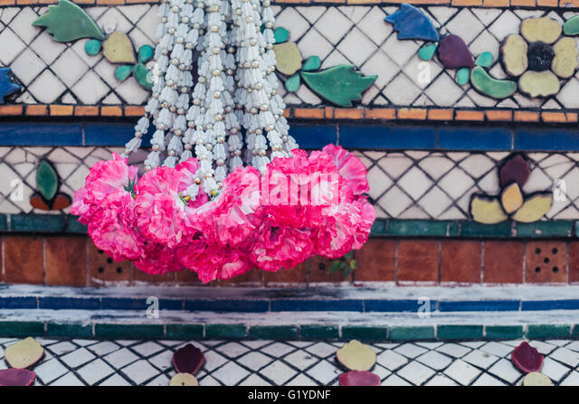 A garland hanging from a Buddhist altar - Stock Image