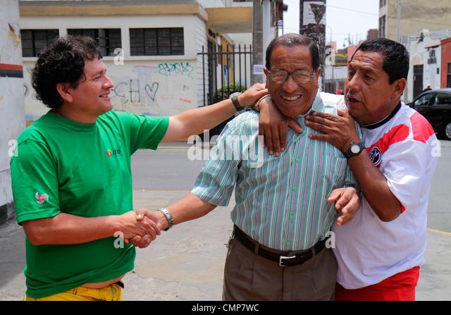 Peru Lima Barranco District Calle Miguel Grau street scene Hispanic man men three handshake greet friends touching - Stock Image
