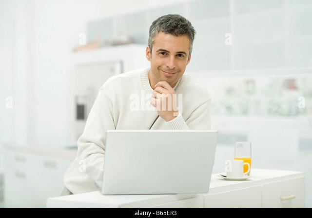 Man using laptop computer in kitchen, smiling at camera - Stock-Bilder