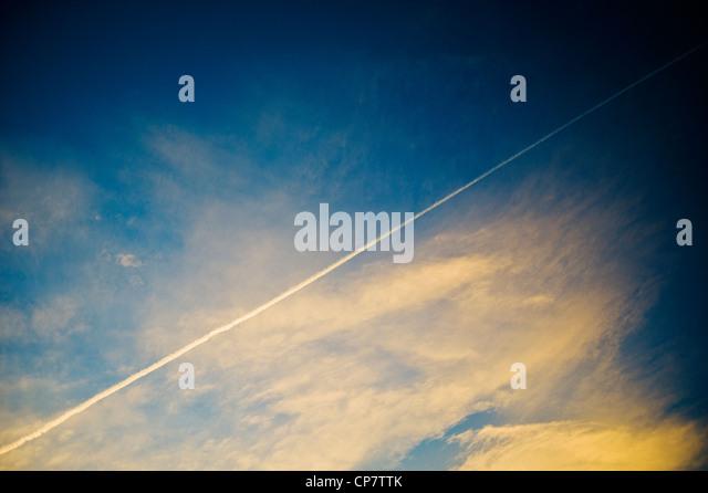 Commercial airline jet contrails across a clear dusk sunset blue sky - Stock Image