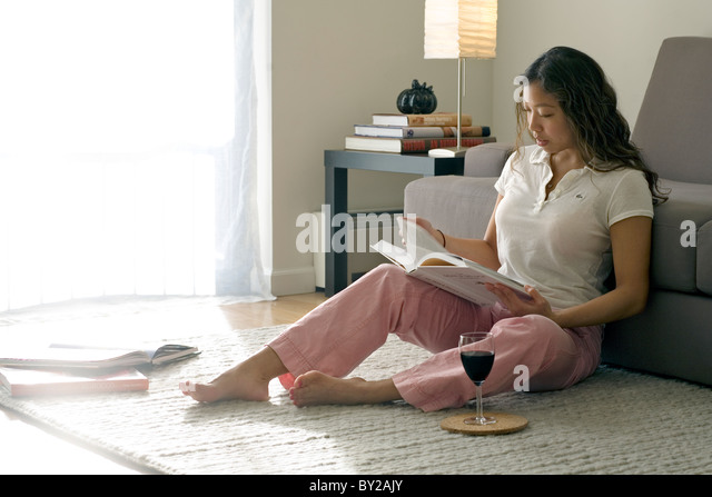 Young woman reading and having a glass of wine at home. - Stock Image