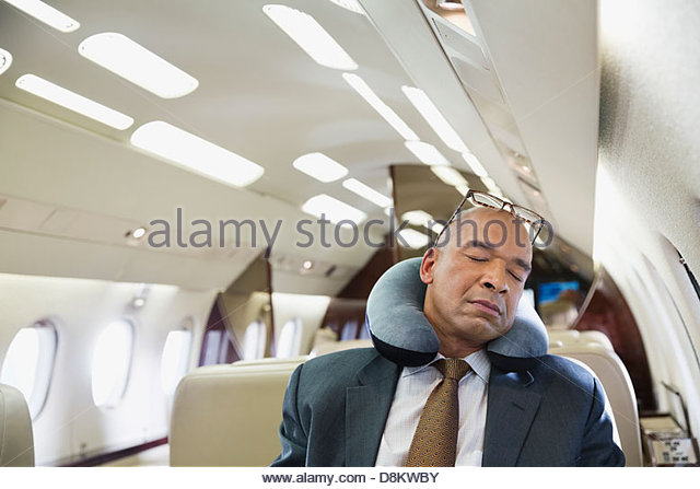 Businessman sleeping in private jet - Stock Image