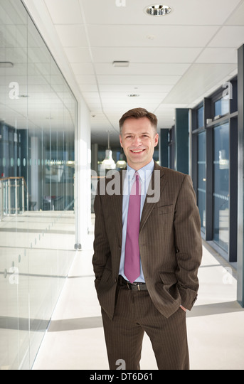 Portrait of businessman in corridor - Stock Image