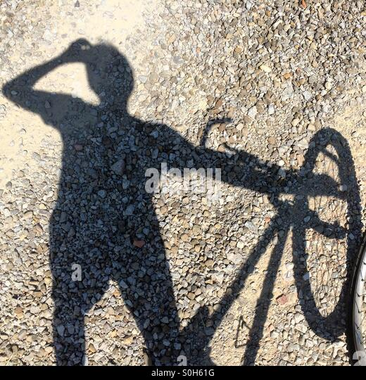 Shadow of a man drinking water standing beside a mountain bike in Tuscany, Italy. - Stock Image