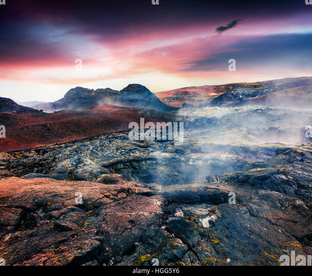 Fields of steamy waters in the Krafla volcano. Colorful exotic sunset with lava ground in the geothermal valley - Stock Image