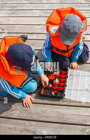 Boys (4-5, 6-7) playing with fishing equipment - Stock Image