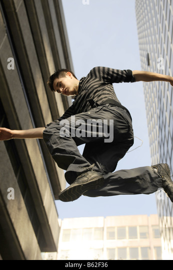 Danny Darwin demonstrating free running (parkour) techniques between office buildings near Embankment, London - Stock Image