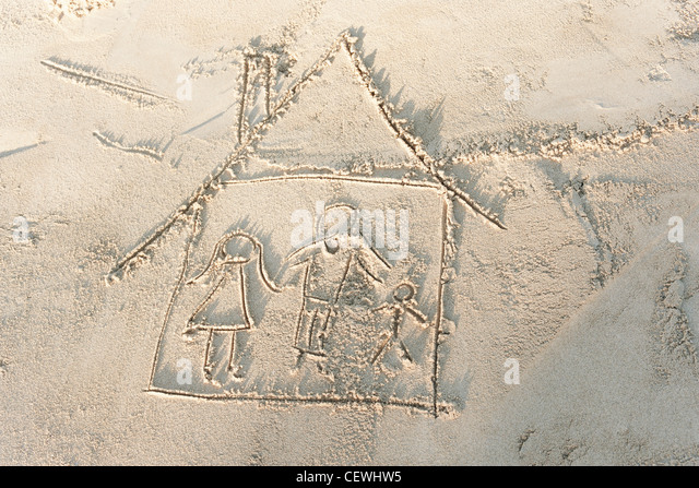 Drawing of family in house in sand, high angle view - Stock-Bilder
