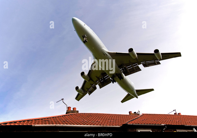 Jumbo jet Boeing 747 landing over rooftops of house at the end of the runway at Manchester airport. - Stock Image