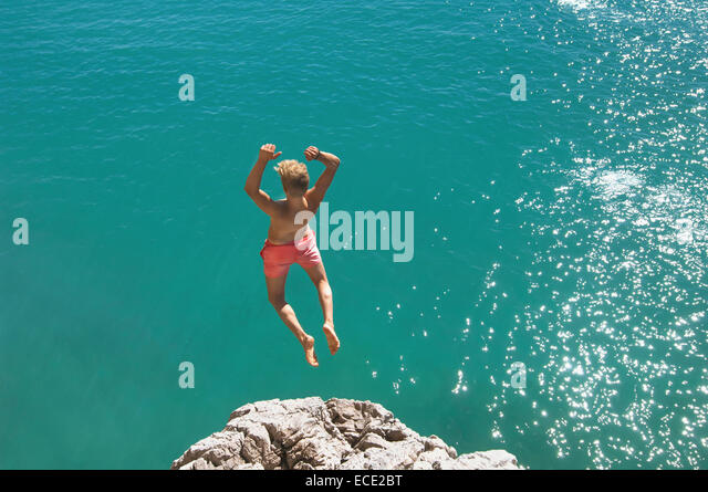 Teenager water cliff sunshine summer holiday jump - Stock Image