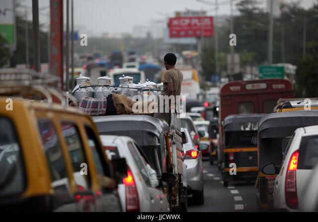Traffic Jam with a milkman standing on his van during a cloudy rainy day in India. - Stock Image