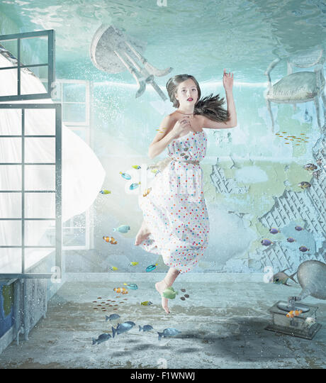 the young beautiful girl underwater in the flooded interior. creative concept - Stock-Bilder