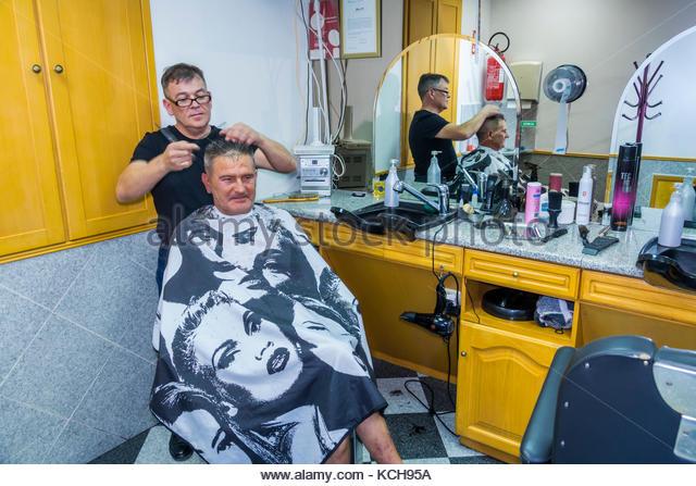 Coimbra Portugal historic center neighborhood barber shop haircut cape mirror reflection interior inside - Stock Image