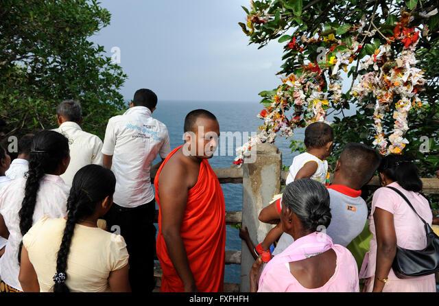 Sri Lanka Trincomalee, Buddhist monk and Tamil Hindu pilgrims at Koneshwaram Hindu temple, view to indian ocean - Stock-Bilder