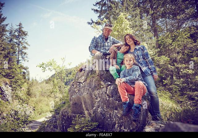 Portrait of family sitting on rock in forest - Stock Image