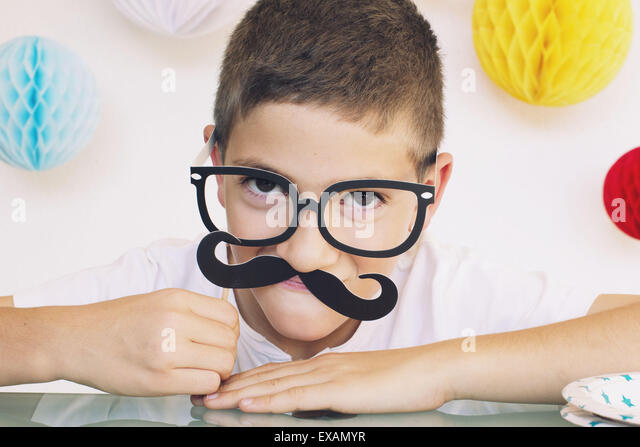 Boy wearing fake mustache and glasses at a birthday party - Stock Image