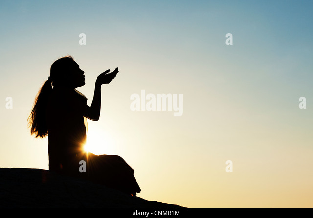 Indian girl sitting holding out her hands at sunset. Silhouette - Stock Image