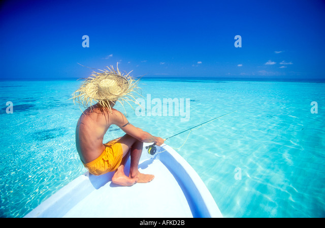 Man with fly fishing rod sitting on boat bow in Belize Caribbean Model and Property Released Image - Stock Image