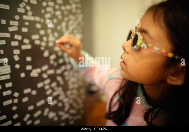 Girl wears sunglasses and plays with magnetic fridge words - Stock Image