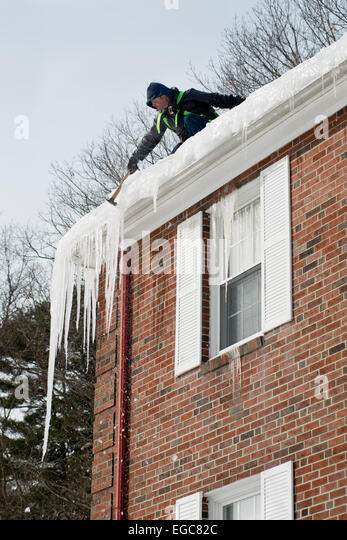 Lexington, MA, USA, 21 Feb, 2015. Contractor chipping hanging ice hanging at the roof of a three story apartment - Stock Image