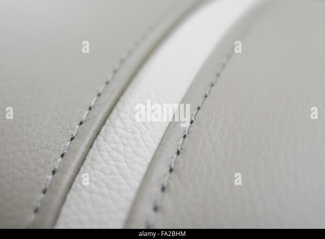 Close up of a stitch on a piece of leather fragment chair upholstery. - Stock Image