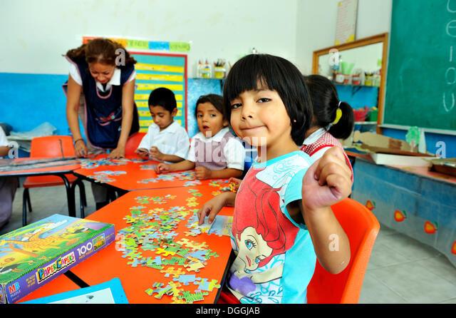 Girl in preschool doing a puzzle, Queretaro, Mexico, North America, Latin America - Stock Image