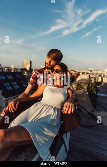 Austria, Vienna, Young couple enjoying romantic sunset on rooftop terrace - Stock-Bilder