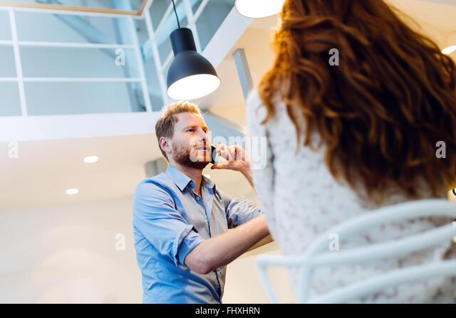 Talking on phone while dating woman is not recommended - Stock Image