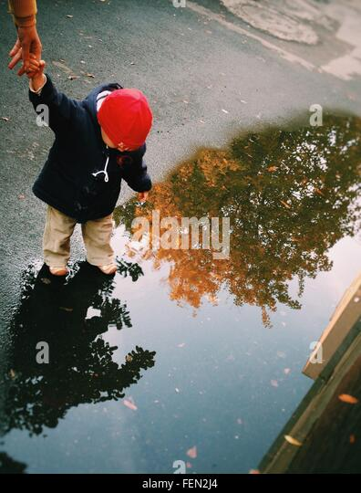 Cropped Image Of Mother Holding Baby Hand By Puddle On Street - Stock Image