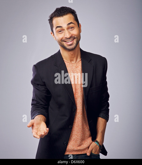 Gesturing cool guy in a studio with one hand in his pocket - Stock-Bilder