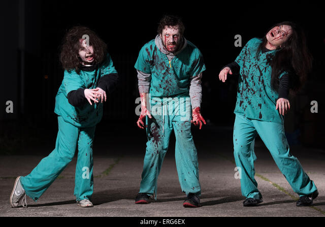 Three zombies covered in blood. - Stock Image