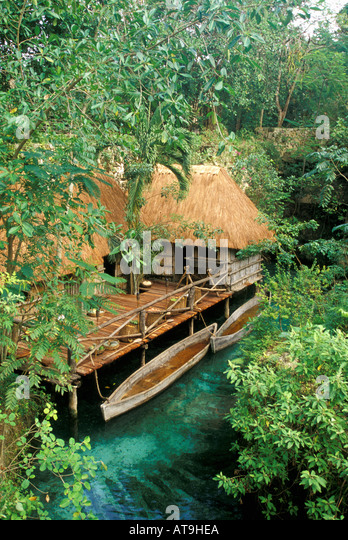 cancun area mexico xcaret park maya village huts canoes over spring - Stock Image