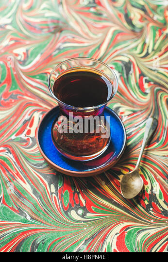 Turkish tea in traditional tulip glass and spoon, colorful background - Stock Image