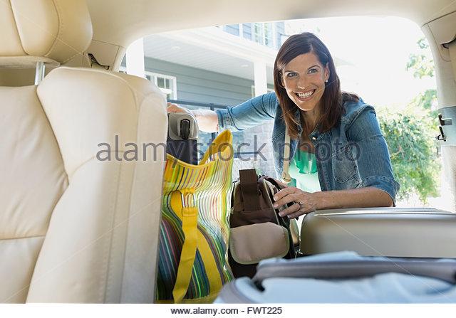 Happy woman loading luggage into minivan - Stock Image