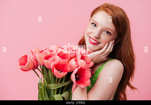 Young beautiful smiling woman holding tulips near face isolated - Stock Image