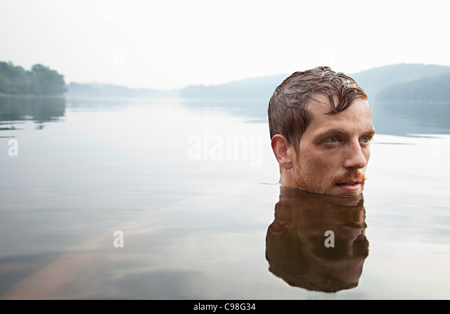 Mid adult man swimming lake - Stock Image