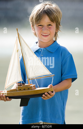 Boy with a toy boat - Stock Image