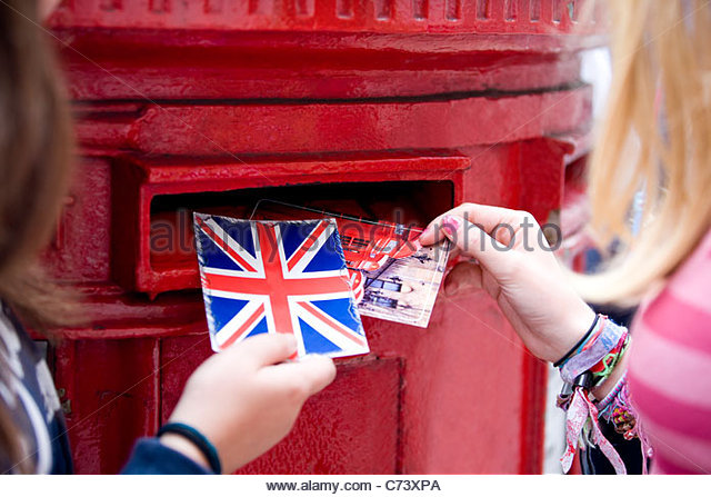 Two teenage girls putting postcards into a red letterbox - Stock Image