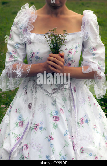 a woman is holding a self picked bouquet of wild flowers in her hands - Stock-Bilder