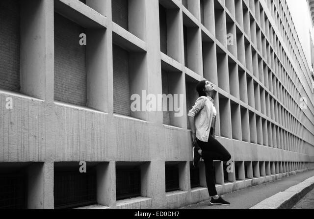 Italy, Milan, Woman leaning against wall - Stock Image