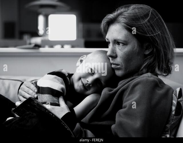 Cute Boy Lying On Mother In House - Stock Image