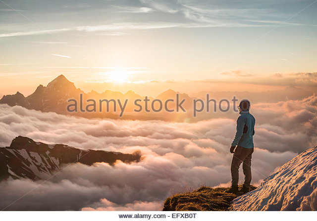 Young male mountain trekker looking at sunrise above clouds, Bavarian Alps, Oberstdorf, Bavaria, Germany - Stock-Bilder