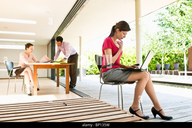 3 business people in modern location - Stock Image