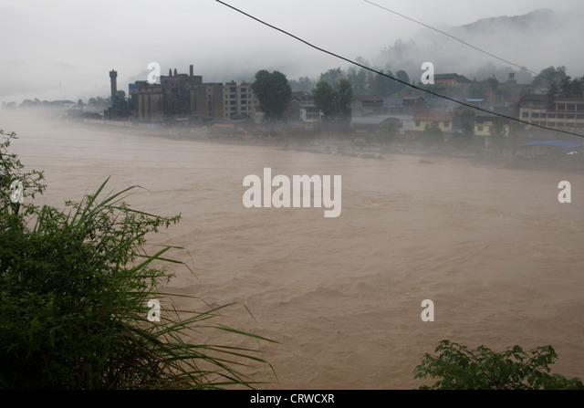 A river swells and overflows its banks and floods a town during widespread flooding in Gaungyaun in north Sichuan - Stock Image
