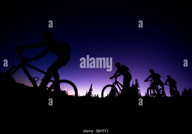 four mountain bikers in a row at dusk - Stock Image